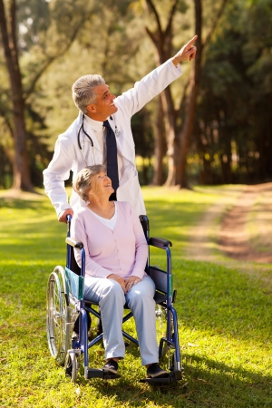 caring mid age doctor taking disabled senior patient for a walk outdoors photo