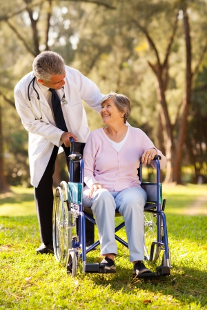 middle aged doctor pushing happy senior patient in wheelchair outdoors photo