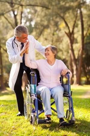 cheerful senior patient doing high-five with friendly caregiver outdoors photo