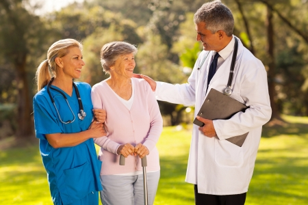garden staff: caring male doctor talking to recovering senior patient outdoors in hospital garden