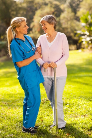 care giver: friendly middle aged caregiver talking to senior woman outdoors