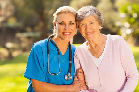 care giver: mid age medical nurse and senior patient outdoors