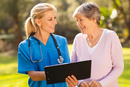care giver: caring caregiver and senior patient outdoors Stock Photo