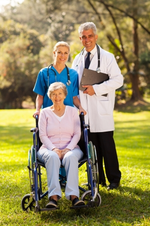 garden staff: caring healthcare workers outdoors with disabled senior patient