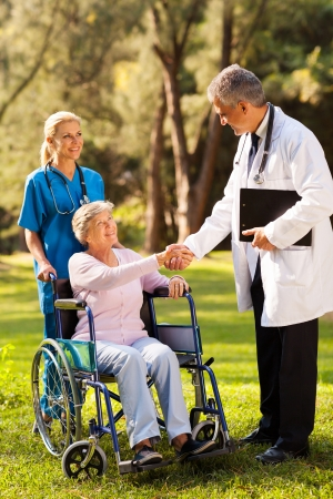 garden staff: friendly male doctor greeting senior patient outdoors Stock Photo
