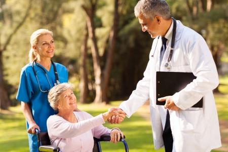 enfermera con paciente: alegre m�dico apret�n de manos con el paciente mayor al aire libre Foto de archivo