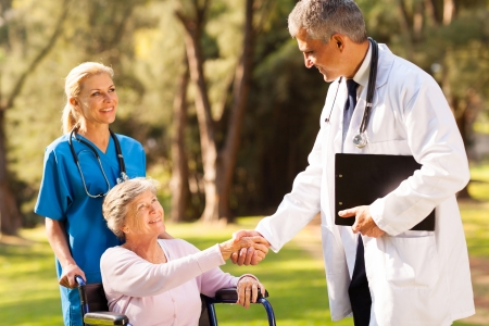doctor and patient: cheerful medical doctor handshaking with senior patient outdoors