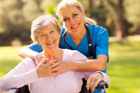 care giver: happy senior woman in wheelchair outdoors with caring caregiver