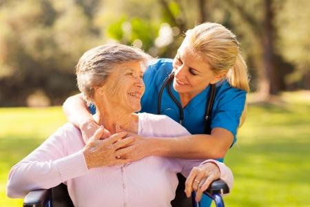 senior health: caring nurse with senior patient outdoors