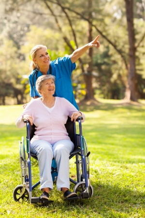 care giver: friendly nurse taking disabled elderly patient for a walk