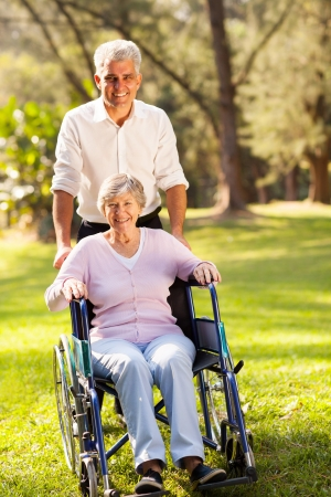 caring mid age son taking disabled senior mother for a walk outdoors in forest photo