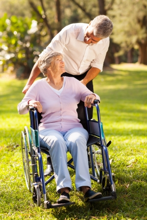 loving middle aged son taking his disabled mother for a walk at the park photo