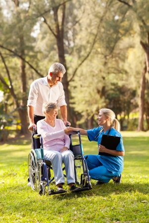 care giver: pretty female doctor greeting recovering senior patient in wheelchair outdoors