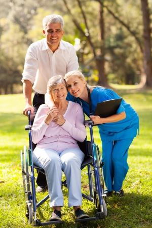 care giver: caring nurse hugging senior patient outdoors Stock Photo