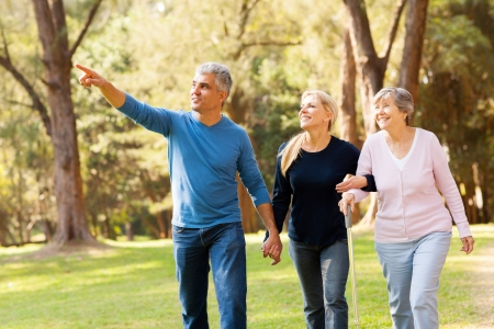 middle aged: cheerful middle aged couple taking elderly mother for a walk in forest Stock Photo