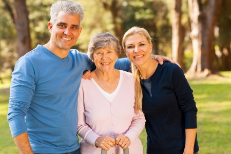 senior adult man: loving mid age couple and senior mother outdoors in forest