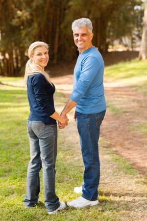 cute senior couple holding hands and looking back photo