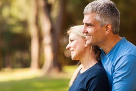 parejas felices: amante esposo de mediana edad con la mujer al aire libre mirando hacia adelante