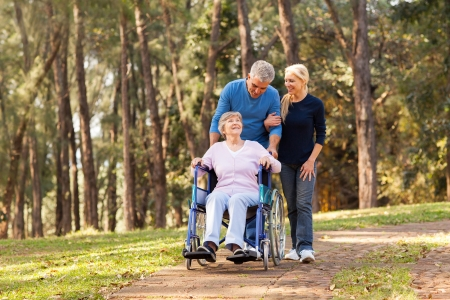 the walk: caring couple taking their disable senior mother for a walk at the park