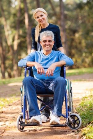 persona en silla de ruedas: amante esposa teniendo su marido discapacitado a caminar en el parque Foto de archivo