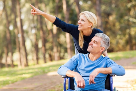 disabled seniors: loving mid age wife taking injured husband for a walk outdoors