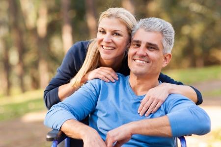 persona en silla de ruedas: amar a la esposa de mediana edad y con discapacidad marido al aire libre Foto de archivo