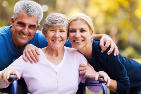 persona en silla de ruedas: Retrato de pareja de mediana edad y mayores madre al aire libre Foto de archivo