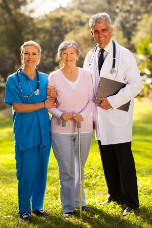 clinical staff: caring medical staff and senior patient outdoors
