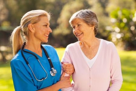 paciente: enfermera cuida a hablar con mayor mujer al aire libre Foto de archivo