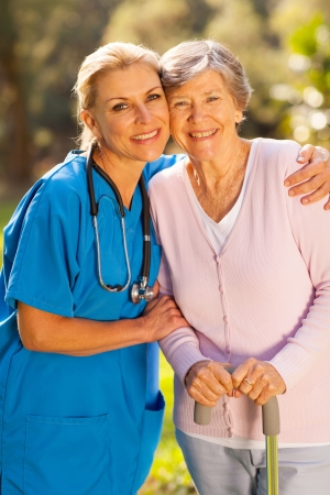 doctor and nurse: friendly mid age caregiver hugging senior patient outdoors Stock Photo