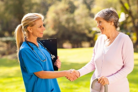 care giver: beautiful mid aged nurse handshaking senior patient outdoors