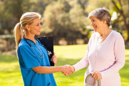 home healthcare: beautiful mid aged nurse handshaking senior patient outdoors