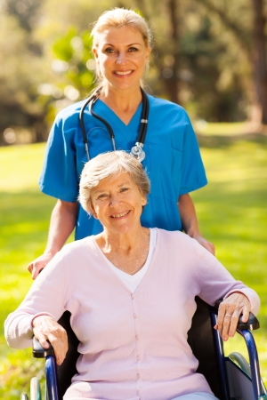 care giver: smiling medical nurse with disabled patient outdoors