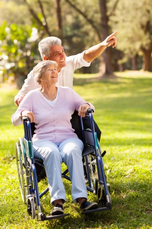 caring mid age son taking senior mother for a walk photo