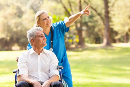 beautiful healthcare worker taking disabled patient for a walk outdoors photo