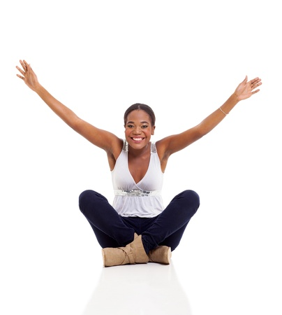 cheerful young afro american woman sitting on floor with her arms up