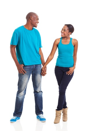 lovers holding hands: beautiful young african american couple standing on white background