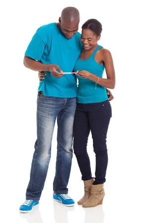prueba de embarazo: feliz pareja africana joven mirando la prueba de embarazo juntos