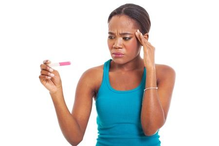 prueba de embarazo: Mujer africana confundido mirando prueba de embarazo aislado en blanco Foto de archivo