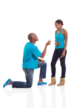 happy african man down on his knee proposing to girlfriend when she is pregnant  photo
