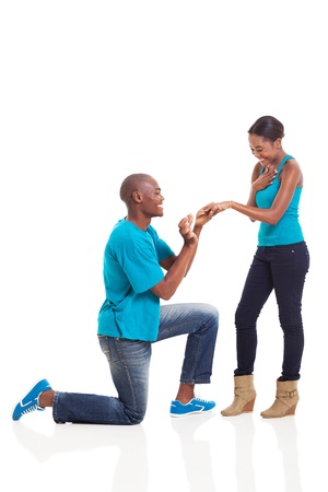 African man putting engagement ring on his excited girlfriend after she said yes isolated on white photo