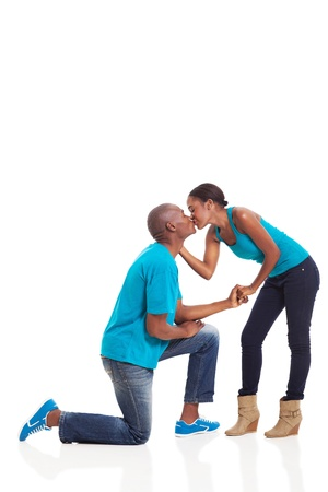 proposed: African American woman kissing her boyfriend after he proposed isolated on white background