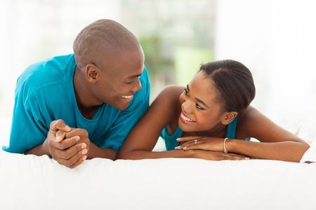 jovenes enamorados: alegre pareja africana acostada en la cama Foto de archivo