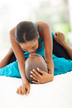 young couple kissing: intimate african couple kissing in bedroom Stock Photo
