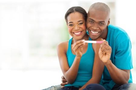 prueba de embarazo: alegre pareja áfrica que muestra la prueba de embarazo positiva Foto de archivo
