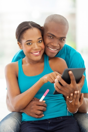 casado joven afroamericano en busca de informaci�n sobre el embarazo en la computadora de la tableta photo