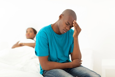 boy bedroom: unhappy african man having a fight with wife in bedroom Stock Photo