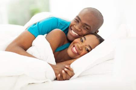 lovers in bed: portrait of happy african couple in bed Stock Photo