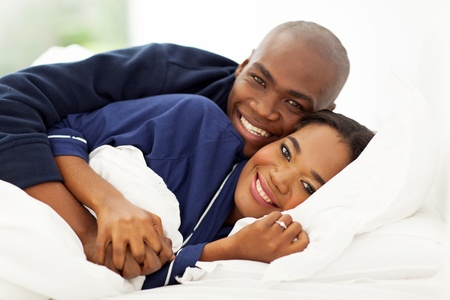 lovely african american couple sleeping in bed photo