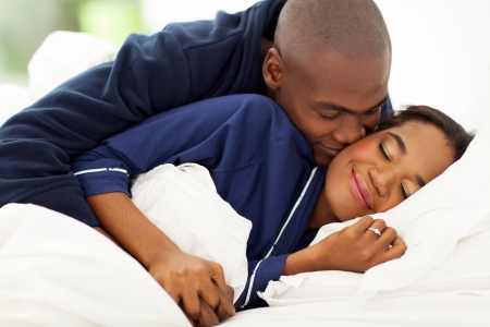 smiling african man in bed kissing wife in bed photo